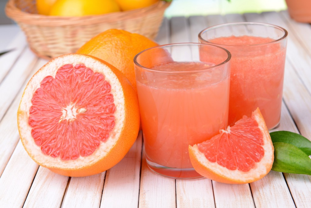 Ripe grapefruit with juice on table close-up